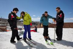 Mature man and young woman with ski instructors on ski slope - stock photo