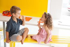 Brother and sister eating ice lollies on bench indoors - stock photo