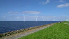 Cyclists across the dike along offshore and onshore Windpark Stock Footage