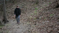 Upset young man walking in forest, throwing stone with annoyance, helpless anger Stock Footage