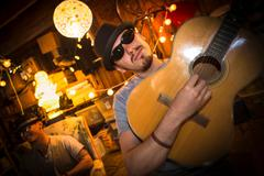 Man wearing hat and sunglasses playing guitar Stock Photos