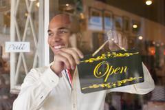 Shopkeeper turning open sign on vintage shop door Kuvituskuvat