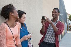 Young man photographing female friends on cell phone Stock Photos