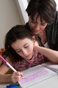 Mother watching daughter writing Stock Photos