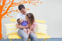 Father sitting on bench with two daughters on lap - stock photo