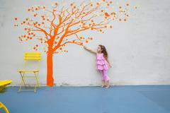 Girl pointing to orange tree mural on wall - stock photo