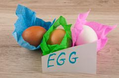 title and chicken eggs in paper laying on wooden table - stock photo