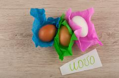 top view title and chicken eggs in paper laying on wooden table - stock photo