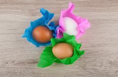 three chicken eggs in colored paper wrapper laying on wooden table. Top view - stock photo