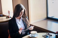 businesswoman working on tablet computer while drinking coffee in office - stock photo