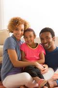 Daughter sitting on parents laps, portrait Stock Photos