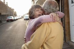 Husband and wife hugging lovingly on street Stock Photos