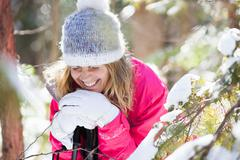 Young adult woman among snow-covered tree branches Stock Photos