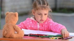 Five-year girl selects the desired color pencil drawing in an album Stock Footage