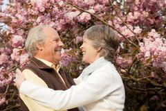 Husband and wife embracing in garden Stock Photos