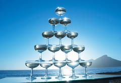 Champagne glasses in pyramid shape with sea in background - stock photo