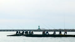 Several fishermen with fishing rods sitting on the pier - stock footage
