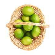 Wicker basket full of multiple ripe limes, composition isolated over the white Stock Photos