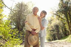 Wife posing with husband holding her straw hat Stock Photos