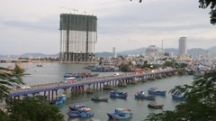 Traffic in a bridge. City bay with blue boats and buildings in the background Stock Footage