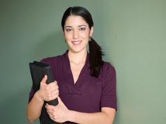 Young woman holding portfolio against green background Kuvituskuvat