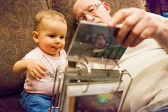 Grandfather and granddaughter looking at photo album Stock Photos