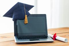 close up of laptop with mortarboard and diploma - stock photo