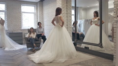 Beautiful Bride at the Clothes Shop for Wedding Dresses, she is Choosing a Dress Stock Footage