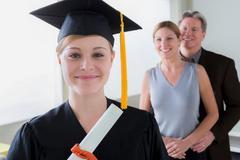 Teenage girl wearing mortarboard with parents in background Stock Photos