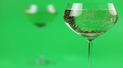 Refocusing glasses of champagne on a green background Stock Footage