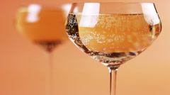 Refocusing glasses of champagne on a cream background Stock Footage
