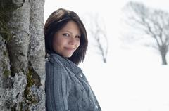 Young female leaning against bare tree in snowy field - stock photo