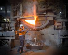 Worker taking sample from furnace in aluminium recycling plant Stock Photos