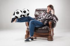 The portrait of fan with balls, holding phone on gray background - stock photo