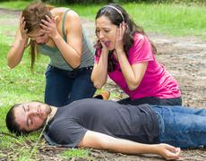 Young man lying down with medical emergency, two young women acting hysterically - stock photo