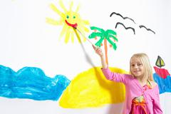 Young girl painting smiling sunshine face on wall Stock Photos