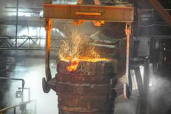 Close up of ladle full of molten metal in industrial foundry Stock Photos