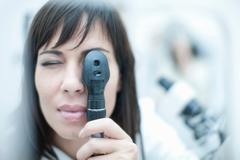 Optician looking through ophthalmoscope Stock Photos