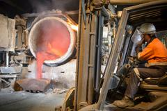 Worker sitting in forklift truck watching furnace in aluminium foundry - stock photo