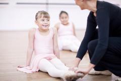 Teacher adjusting feet position of young ballerina Stock Photos