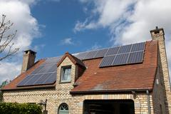 Detached house with solar panels on roof - stock photo