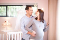 Expectant couple in nursery - stock photo