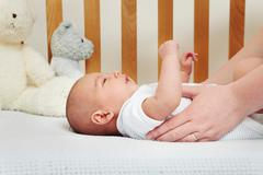 Mother picking up baby from crib Stock Photos