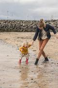 Mother and toddler walking at waters edge Stock Photos