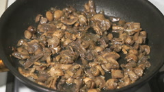 The mix of mushrooms is fried in a black pan Stock Footage