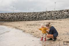 Mother and toddler crouching at waters edge Stock Photos
