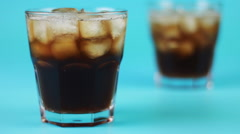 refocusing glass of cola on a blue background - stock footage