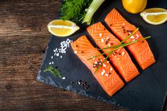 Salmon filet sliced on three parts with lime and herbs. - stock photo