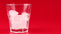 Cola pour into glass on a red background Stock Footage