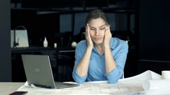 Young female architect having head pain during work on laptop by table in the ki Stock Footage